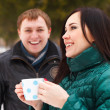 Happy couple having fun in the winter park drinking hot tea — Stock Photo