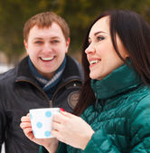 Happy couple having fun in the winter park drinking hot tea — Stockfoto