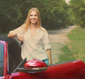 Young woman standing near a sports car holding keys — Stock Photo