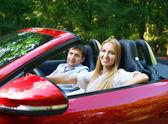 Unga lyckliga par nära den röda bilen — Stockfoto