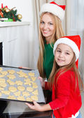 Little girl with her mother baking Christmas cookies — Stock Photo
