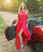 Beautiful blond young woman near a sports car — Stock Photo