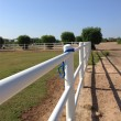 White rail fence on grass bank against blue sky — Stock Photo