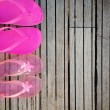Brightly colored pink flip-flops of a mother and daughter on woo — Photo