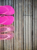 Brightly colored pink flip-flops of a mother and daughter on woo — Stok fotoğraf