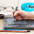Graphic designer working in office with tablet pen — Stock Photo #36097235