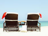 Christmas card or background - couple in sunloungers with Santa — Stock Photo