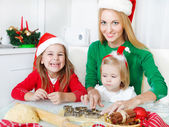 Two adorable sisters with her mother baking Christmas cookies — Stock Photo