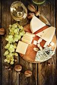 Flaschen und glas weißwein, käse, nüssen und trauben — Stockfoto