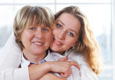 Close up portrait of a mature mother and adult daughter being cl — Stock Photo