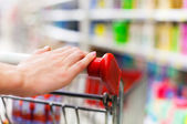 Female shopper with trolley at supermarket — Stock Photo