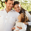 Happy young family with baby girl outdoors — Stock Photo