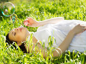 Beautiful pregnant woman relaxing on grass — Stock Photo