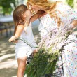 Beautiful and happy young woman on bicycle with her daughter — Stock Photo #39101115