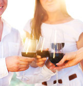 People holding glasses of red wine making a toast — Stock Photo