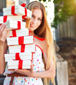 Gift boxes in the hands of young blond woman — Stock Photo