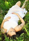 Güzel bir hamile kadın çimenlerin üzerinde rahatlatıcı — Stok fotoğraf