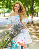 Beautiful and happy young woman on bicycle — Stock Photo
