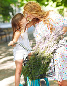 Beautiful and happy young woman on bicycle with her daughter — Stock Photo