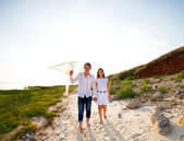 Happy young couple in love with flying a kite — Stock Photo