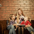Happy mother and her little daughters indoors — Stock Photo