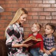 Stock Photo: Happy mother and her little daughters indoors. Brick background
