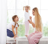 Happy mother and daughters playing in the bedroom — Stock Photo