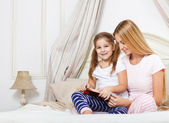 Mother reading bed time story book to her daughter — Stock Photo