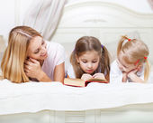 Mother and her daughters reading bed time story book — Stock Photo