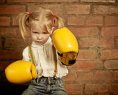 Little girl with yellow boxing gloves over brick wall — Stock Photo