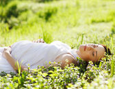 Beautiful pregnant woman on grass in the spring park — Stock Photo