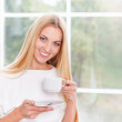 Portrait of lovely young woman having cup of tea at home — Stock Photo #40467381