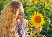 Happy young woman with long hair in the sunflower field — Stock Photo