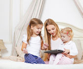Happy mother and her little daughters having fun using a tablet — Stock Photo