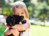 Cute little girl hugging dog puppy — Stock Photo