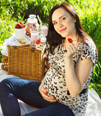 Pregnant woman at picnic in the spring park — Stock Photo