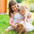 Cute little girl and her mother hugging dog puppies — Stock Photo #40978565