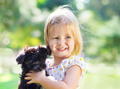 Cute little girl hugging dog puppy outdoors — Stock Photo