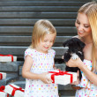 Cute little girl and her mother hugging dog puppies — Stock Photo