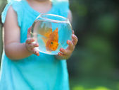 Little baby girl holding a fishbowl with a goldfish on a nature  — Stock Photo