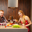 Stock Photo: Happy couple in a kitchen eating pasta in a kitchen
