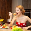 Sexy young blond woman eating spaghetti in the kitchen — Stok fotoğraf