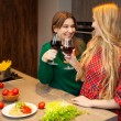 Two beautiful young women friends drinking red wine together — 图库照片