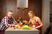 Happy couple in a kitchen eating pasta in a kitchen — Stock Photo