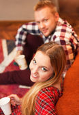 Couple relax at home with cup of coffee in the living room — Stockfoto