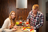 Couple in a kitchen cooking pasta and drinking red wine — Stock Photo