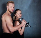 Athletic couple with a dumbells near the wall — Stock Photo