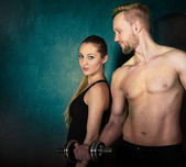Athletic couple with a dumbells near the wall — Stok fotoğraf