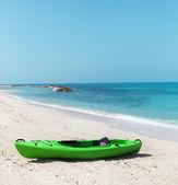Green kayak on the beach — Stock Photo