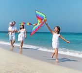 Happy young family with flying a kite — Stok fotoğraf